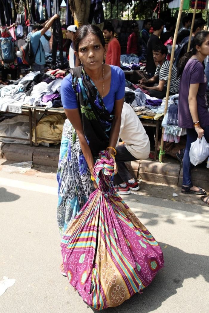 A woman selling old shoes in the weekly clothes market
