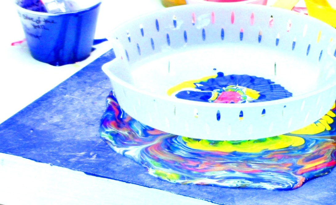 pouring paint on canvas through a colander