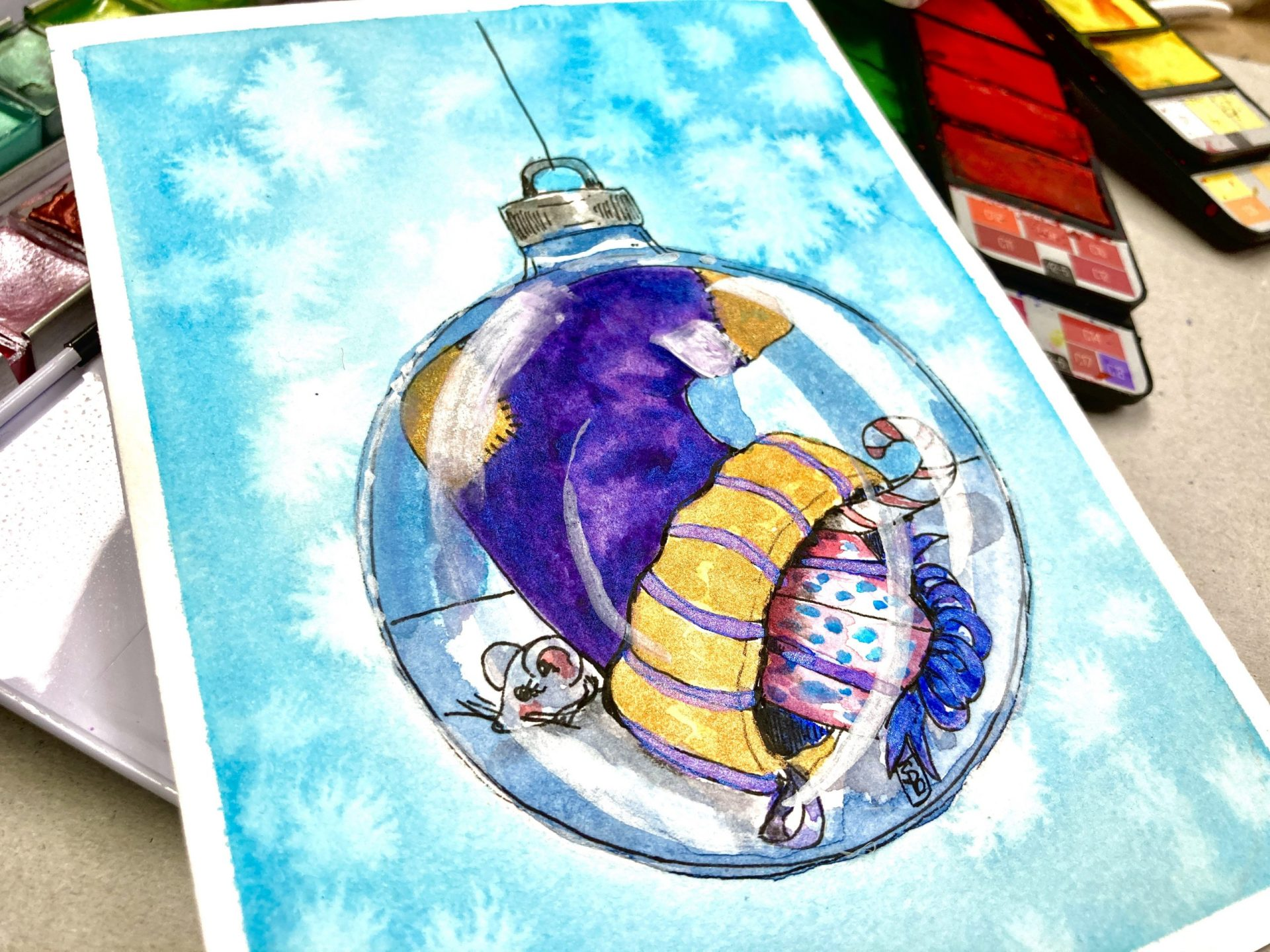 purple and gold Christmas Stocking spilling gift with a little mouse in a clear glass ball ornament