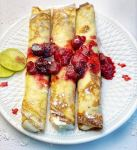 sweet crepes with berry gem on white plate