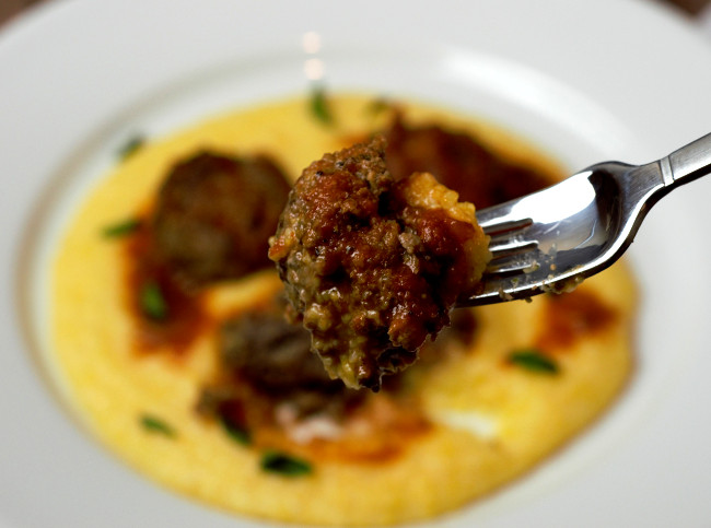 A piece of meatballs on a fork close to the screen with plate of meatballs behind it.
