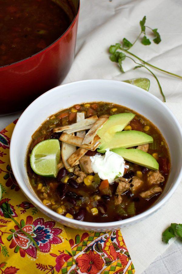 Hearty Bowl of Chicken Tortilla Soup with fresh lime, sour cream, avocado, and crispy tortilla strips.