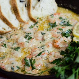 shrimp in butter sauce with bread and lemons