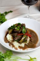 pepper steak on mashed potatoes in white bowl
