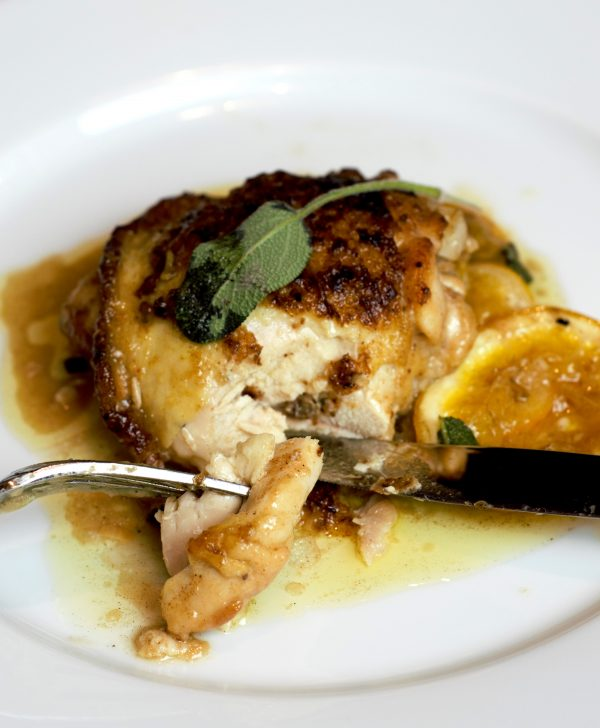 A beautifully browned piece of chicken in a rich lemon butter sauce.