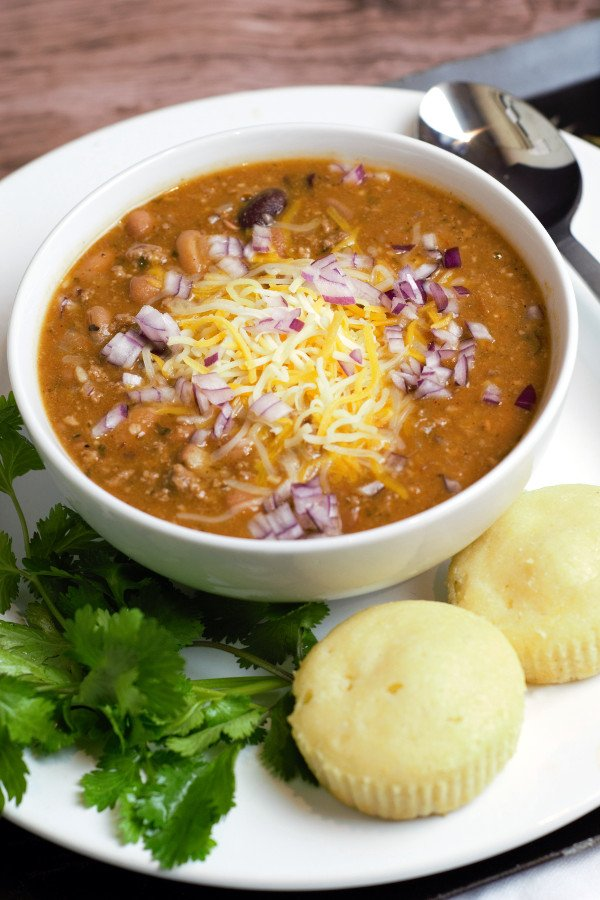 Chili in a white bowl with corn bread and cilantro