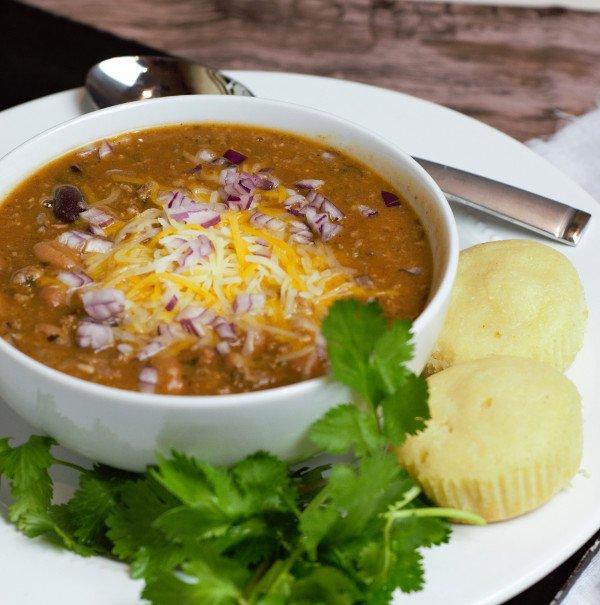 bowl of chili con carne with corn muffins and cilantro