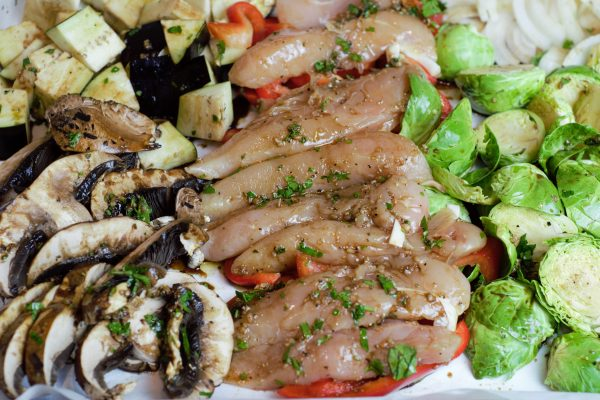 Pan wit chicken and vegetables layed out for roasting and coated in balsamic marinade.