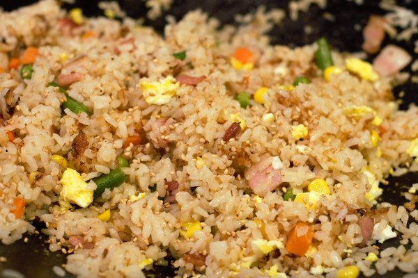 Perfectly cooked fried rice with bacon, eggs, mixed vegetables, soy sauce, sesame oil, and some toasted sesame seeds.