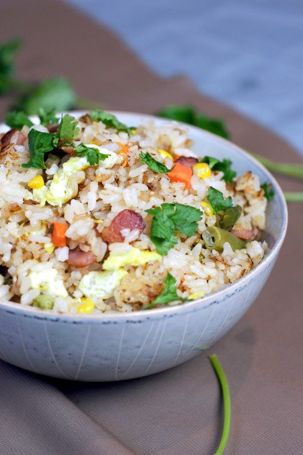 Beautiful bowl of bacon fried rice with gorgeous crispy bacon, mixed vegetables , and perfectly crisp rice.