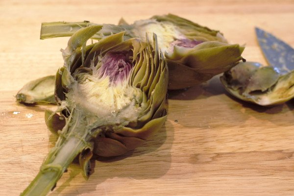 Artichokes halved after steaming. The center of the artichokes are very tender and ready for cleaning.