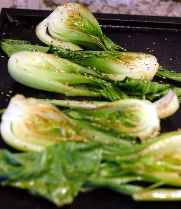 Baby Bok Choy is grilled on one side and brown along the edges.