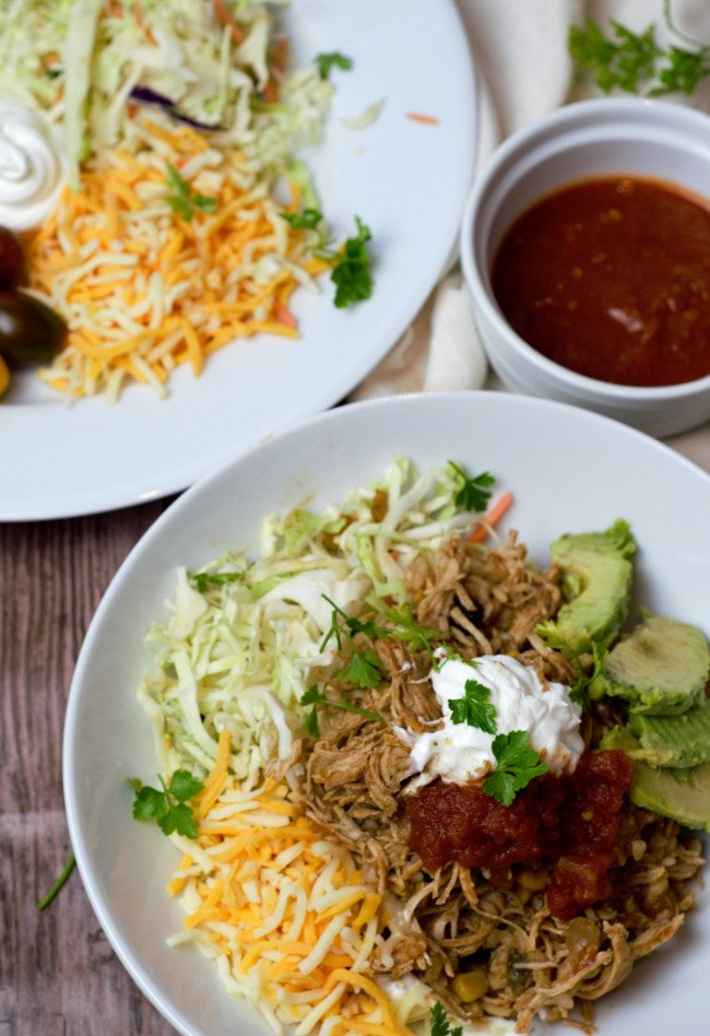 Chicken Taco bowl with a side of salsa and toppings.