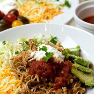 Shredded chicken with avocado, cabbage, sour cream, and salsa