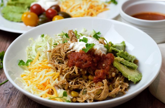 chicken taco bowl served with cabbage, avocado, sour cream, cheese, and red salsa.