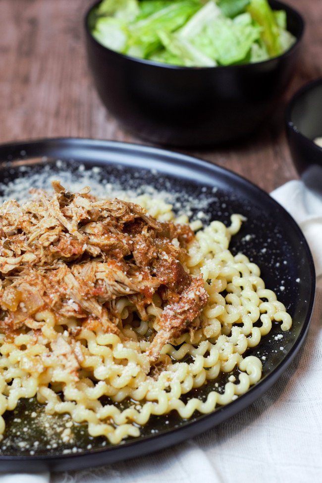 pork ragu on a pile of curly pasta sitting on a black plate.