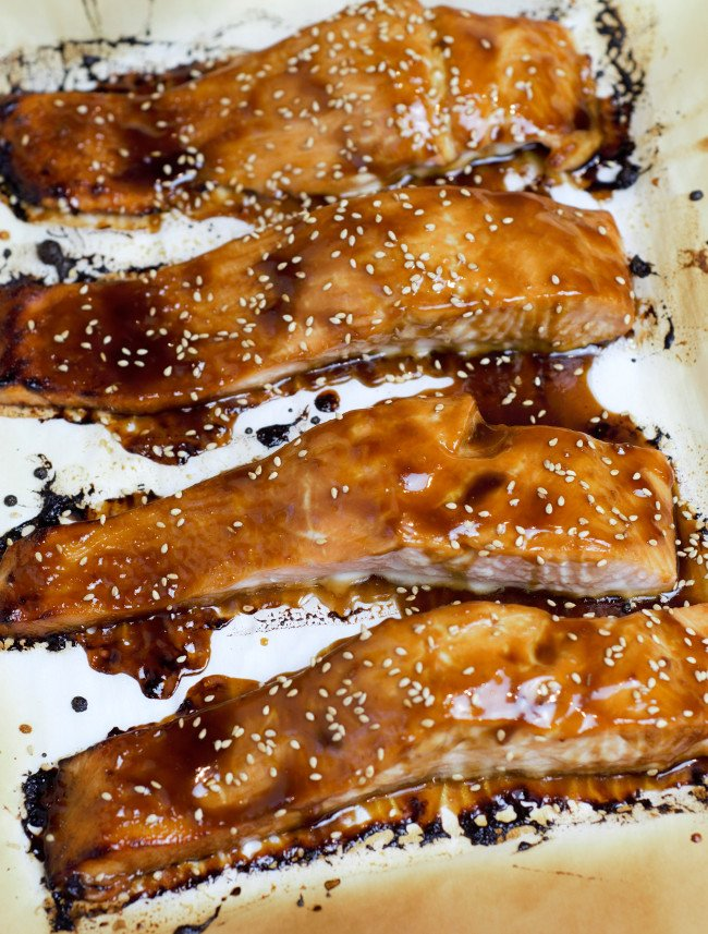 Four pieces of salmon with dark teriyaki glaze on a sheet pan.