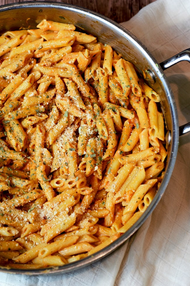 Close up shot of penne pasta in a pan with light tomato sauce and Parmesan on top