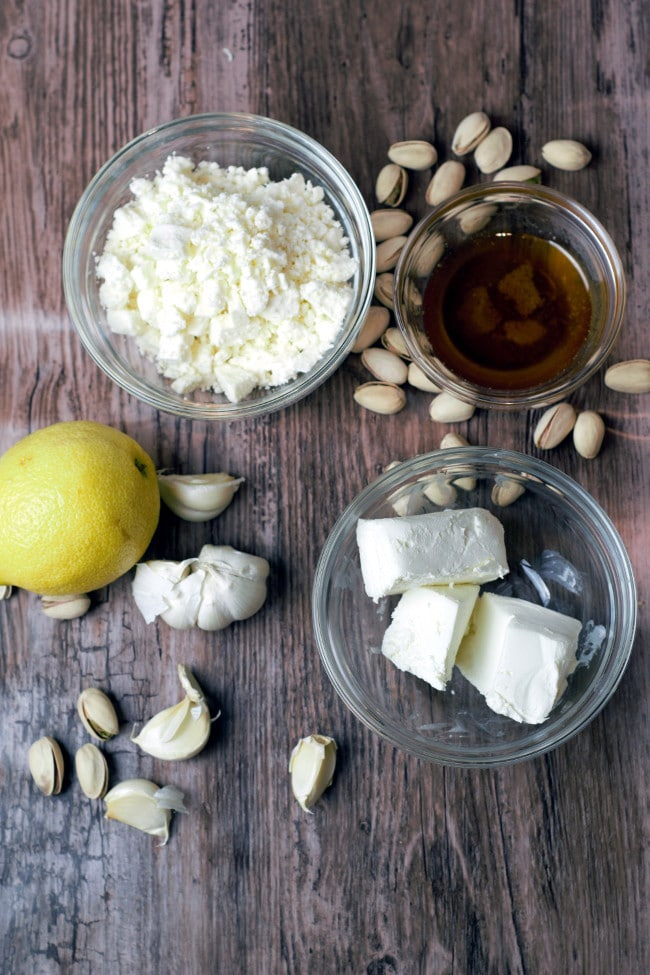 Glass bowl of feta, bowl of cream cheese, honey, lemon, garlic cloves, and in shell pistachios on a wood background.