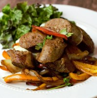 close up italian sausage with peppers and side salad