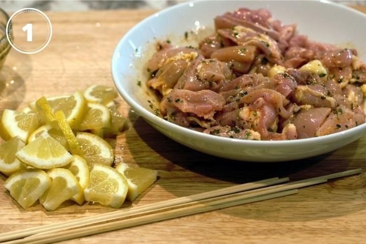 raw chicken in a white bowl with lemons