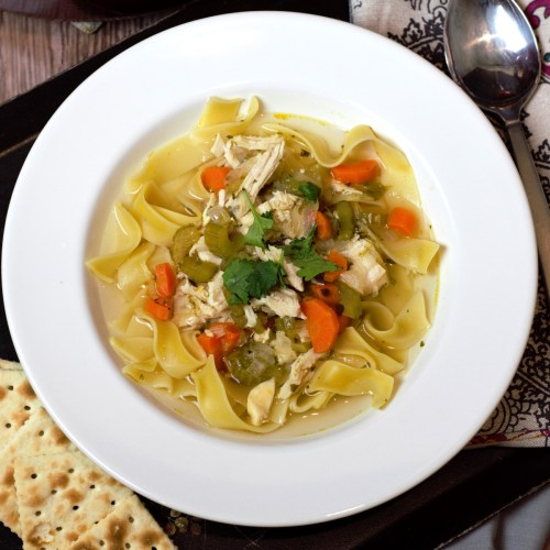 chicken soup in white bowl with saltines