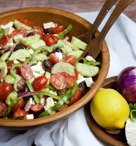 Greek salad in wood bowl with ingredients on side