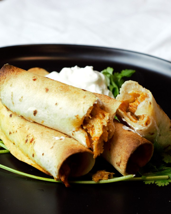 close up taquitos on black plate with sour cream
