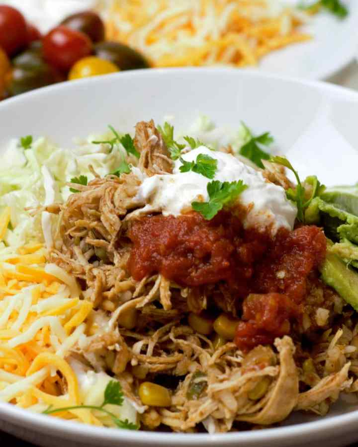 close up shredded chicken filling with taco toppings