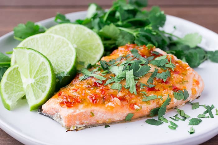 Sweet Chili Salmon on a White Plate with Limes and Cilantro