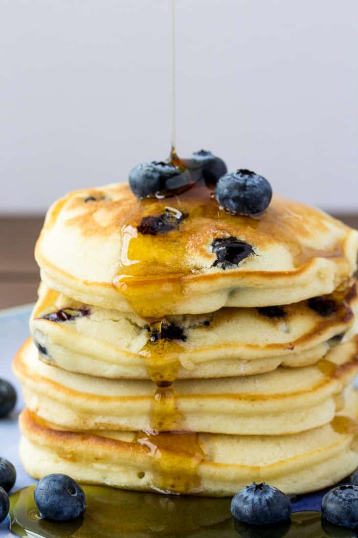 A Stack of Fluffy Blueberry Pancakes with Syrup Being Poured on Top