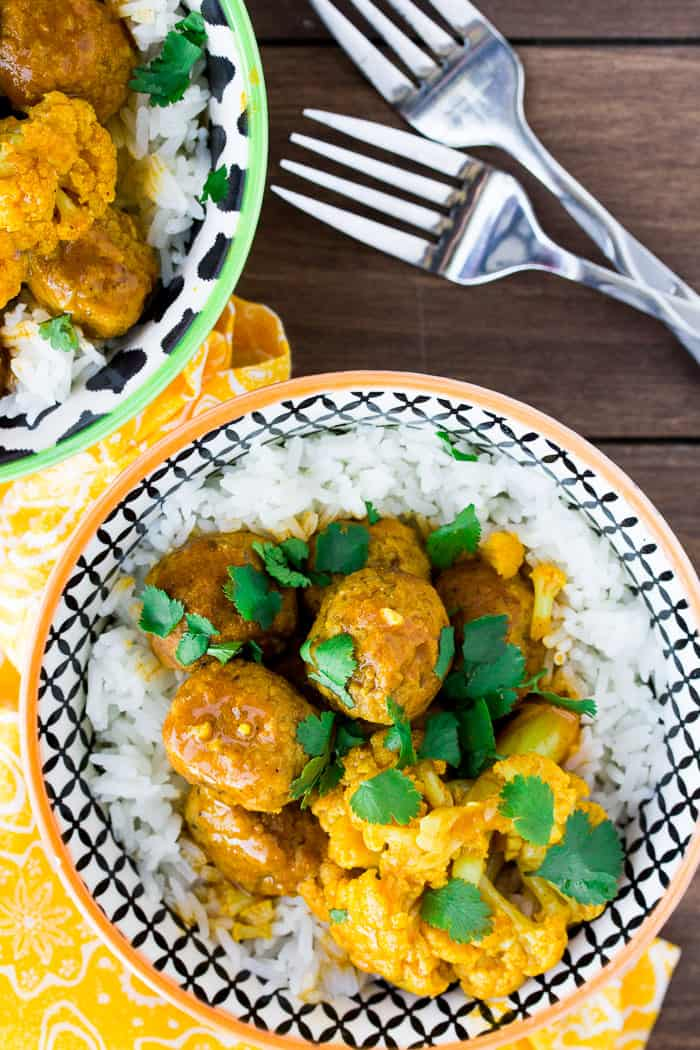 2 Bowls of Coconut Curry Meatballs & Cauliflower with 2 Forks on a Wooden Board