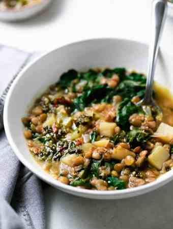 green lentils in a white bowl with steamed chard and spoon