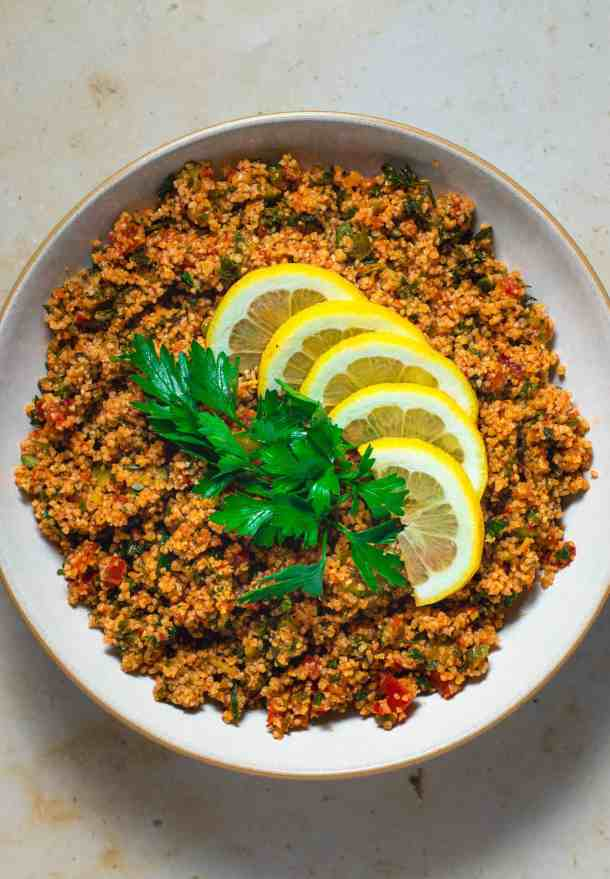 A large bowl of kisir salad topped with lemon slice and parsley leaves