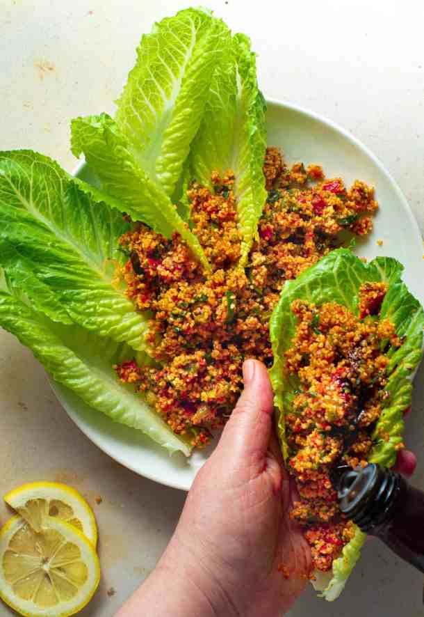 kisir in lettuce leave hand hondling one lettuce leaf pour pomegranate molasses