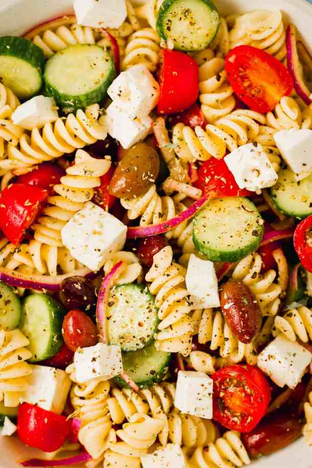 fusilli pasta, cherry tomatoes, cucumbers, feta and red onions in a close up photo