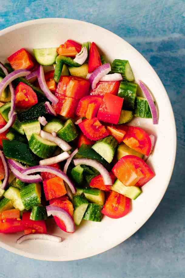 tomatoes, cucumber, and red onions chopped in a white bowl