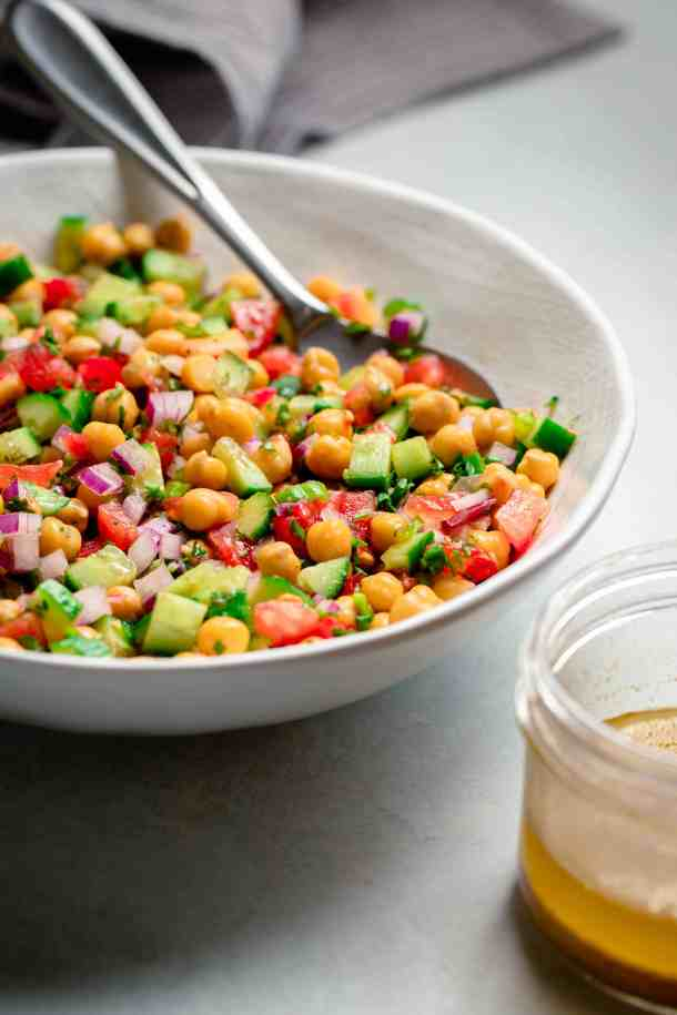A white bowl of chickpea, tomatoes, cucumbers marinated in a lemony dressing