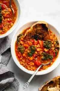 A bowl of mediterranean lentil soup with a piece of sour dough