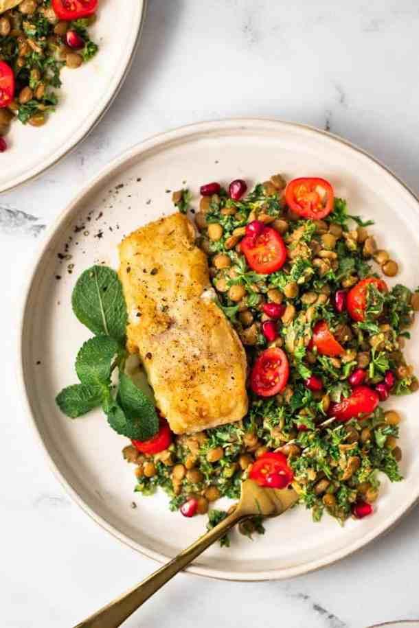 Close up photo of fried fish on a lentil salad