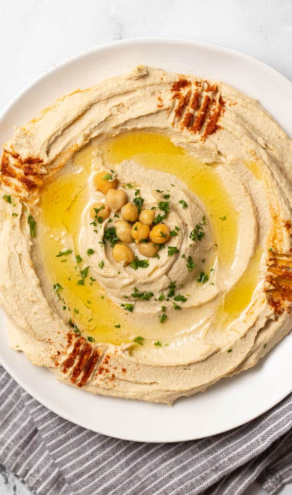 closeup of authentic hummus swirled on a plate with chickpeas, olive oil and paprika