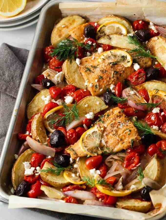 Greek Sheet pan Cod Dinner- A sheet pan filled with cod, roasted potatoes, cherry tomatoes, shallots, black olives and feta