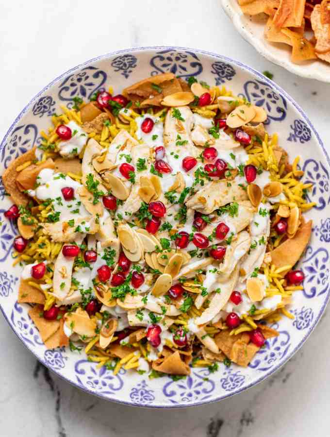 Chicken fatteh in a decorative bowl topped with pomegrantes, almonds, and parsley