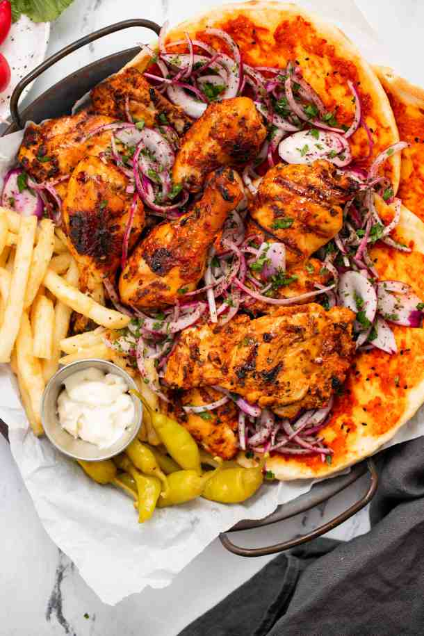 Close up of harissa BBQ chicken on a platter with fries, garlic mayo, sumac onions, and naan bread
