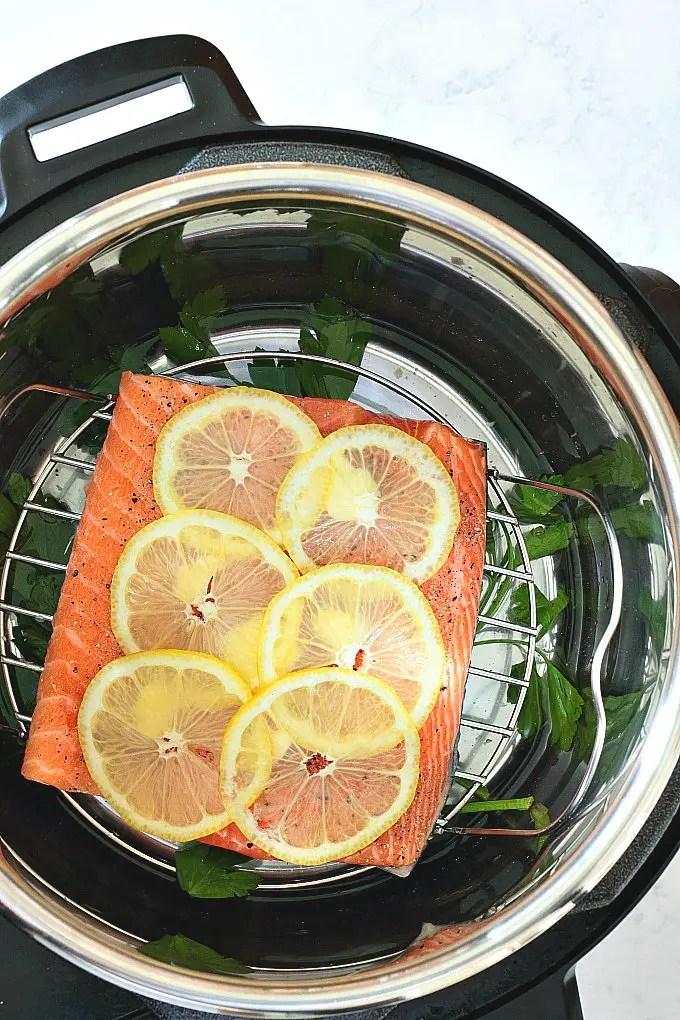 lemon pepper salmon filet topped with lemon in Instant Pot