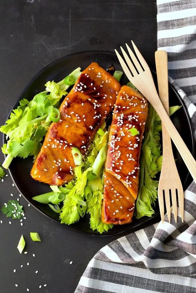 Asian teriyaki salmon on black plate with fresh greens