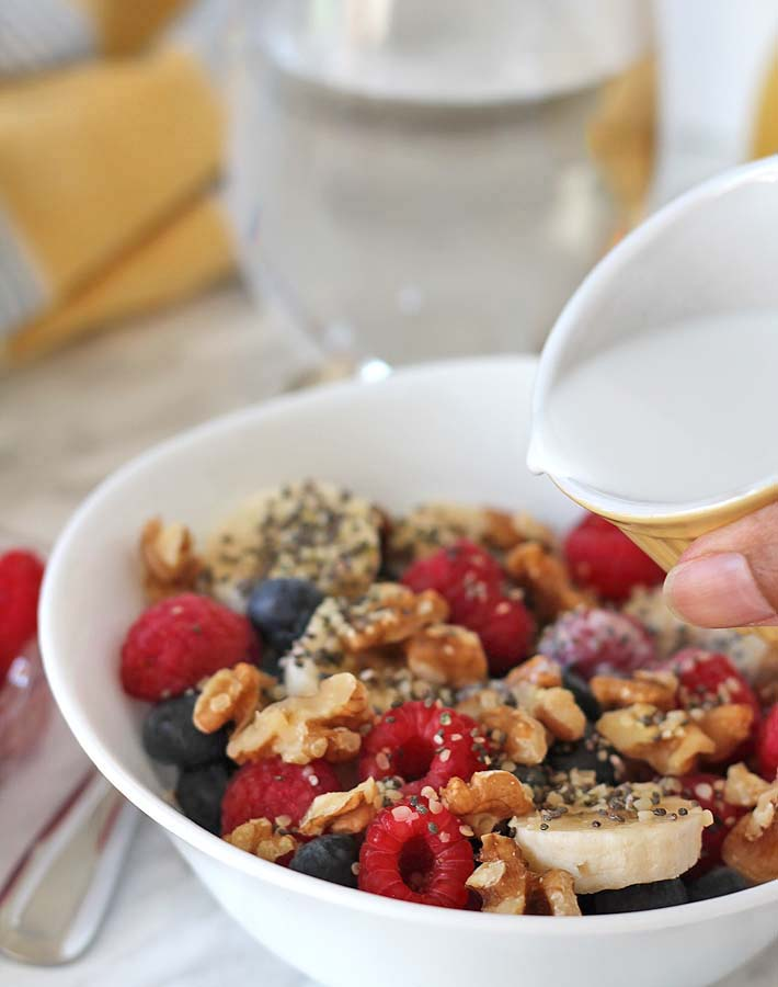 Berry Coconut Breakfast Bowl with coconut milk in a ramekin just about to be poured on top of the bowl contents