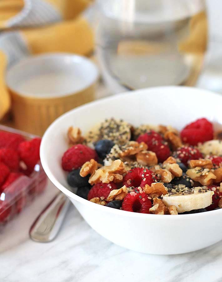 A Berry Coconut Breakfast Bowl sitting on a white marble surface