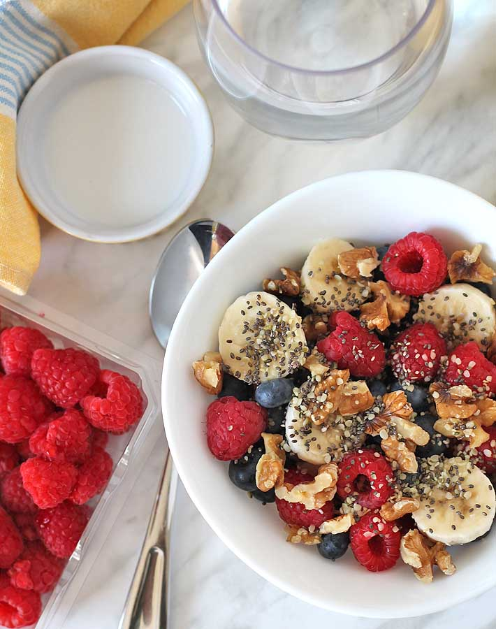 Oerhead shot of a Berry Coconut Breakfast Bowl with a spoon sitting beside the bowl