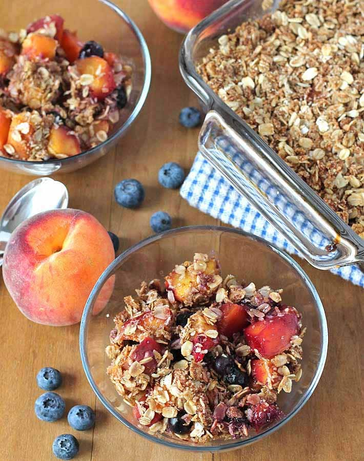An overhead shot of Vegan Peach Blueberry Crisp in two bowls and the baking dish set off to the side
